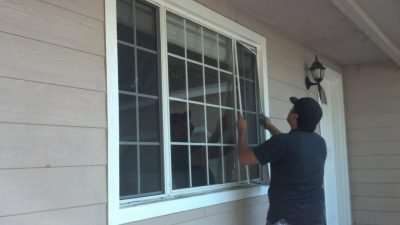 window screens installer with black baseball cap